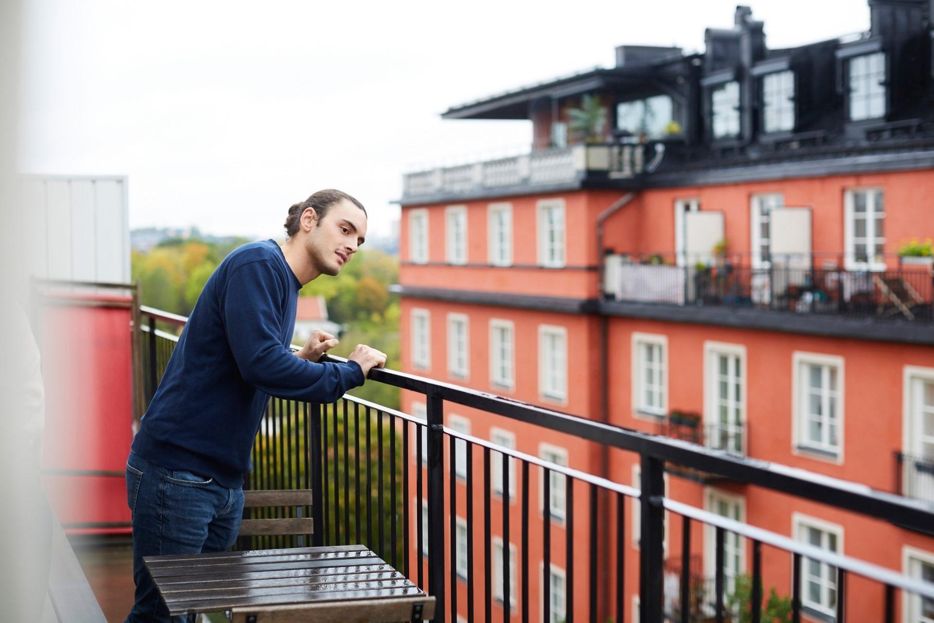 Ung mann står å ser ut fra balkong