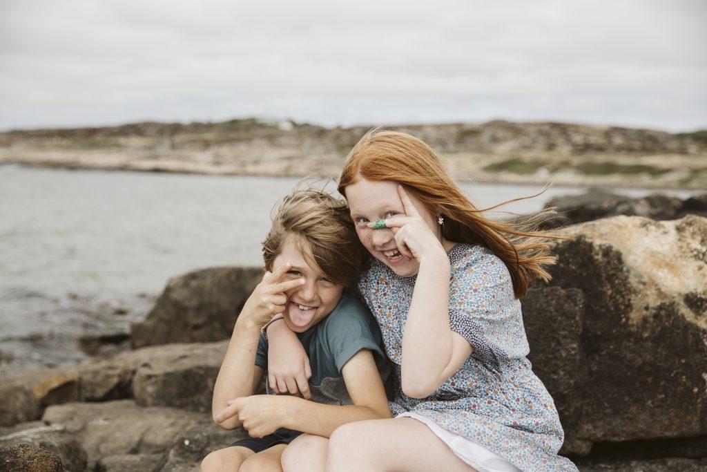 Søsken som smiler på svaberget ved havet.