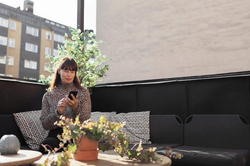 Dame på veranda med mobilen