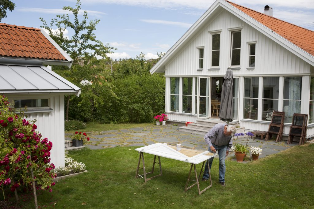 Mann maler dør i hagen foran