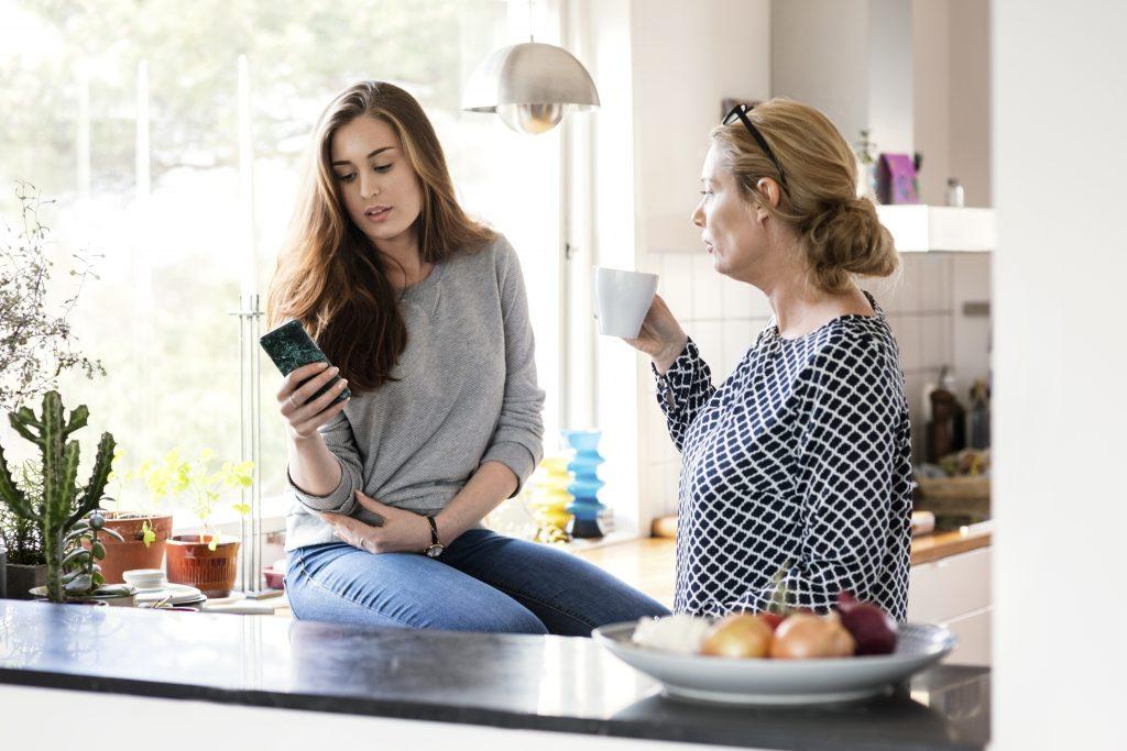Jente med mobil, mor med kaffekopp på kjøkken