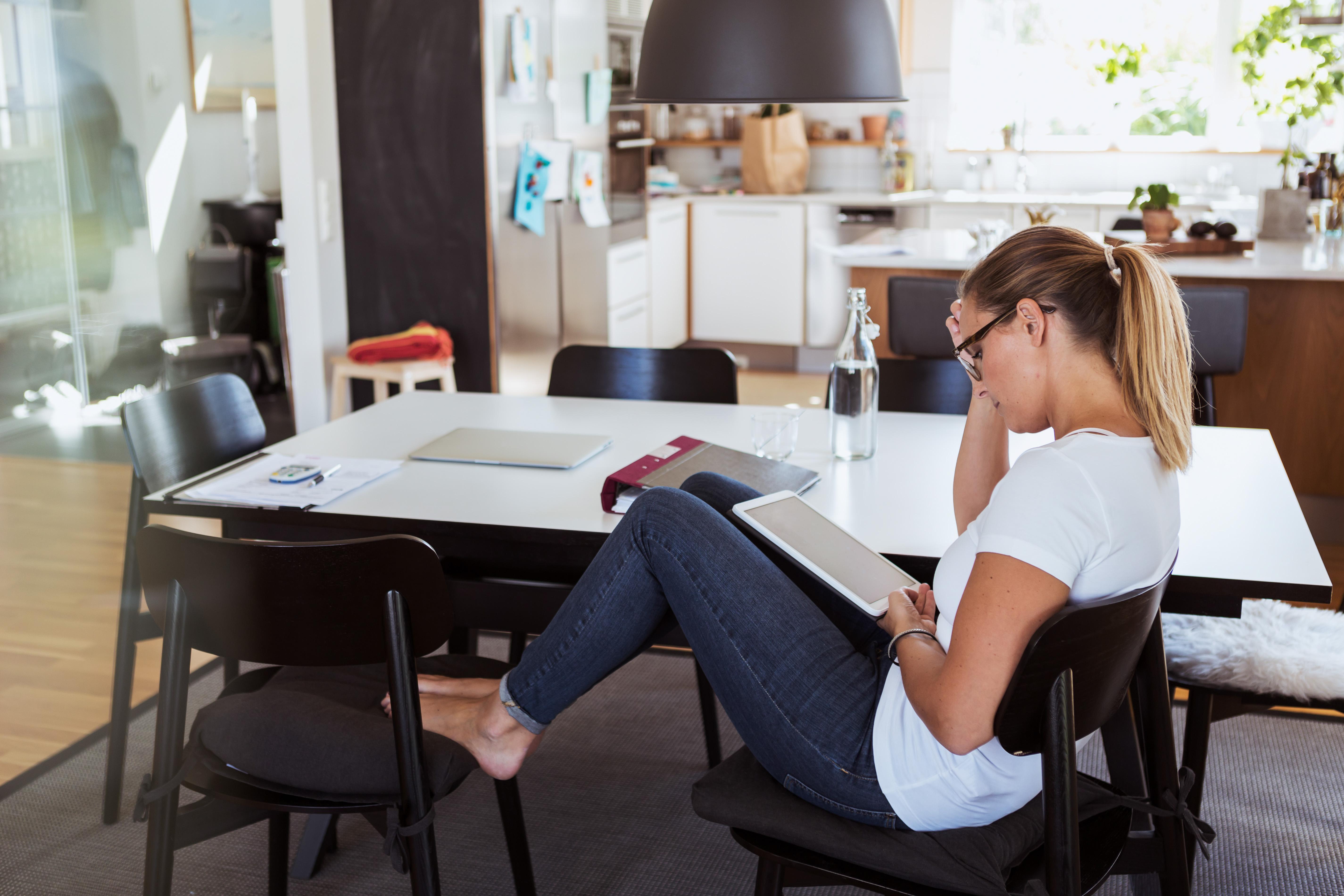 Kvinne leser på tablet ved kjøkkenbordet hjemme