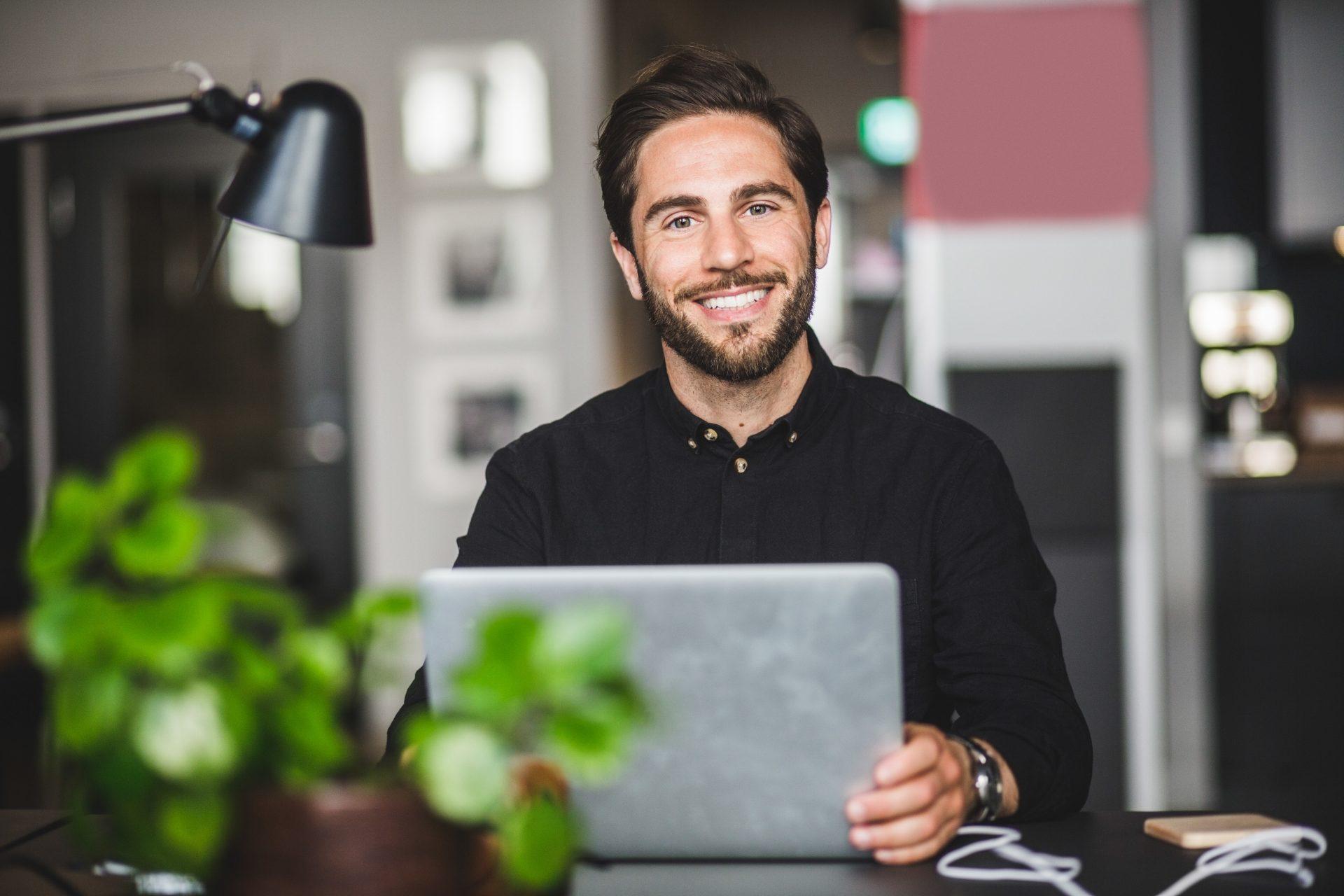 Mann smiler foran PC