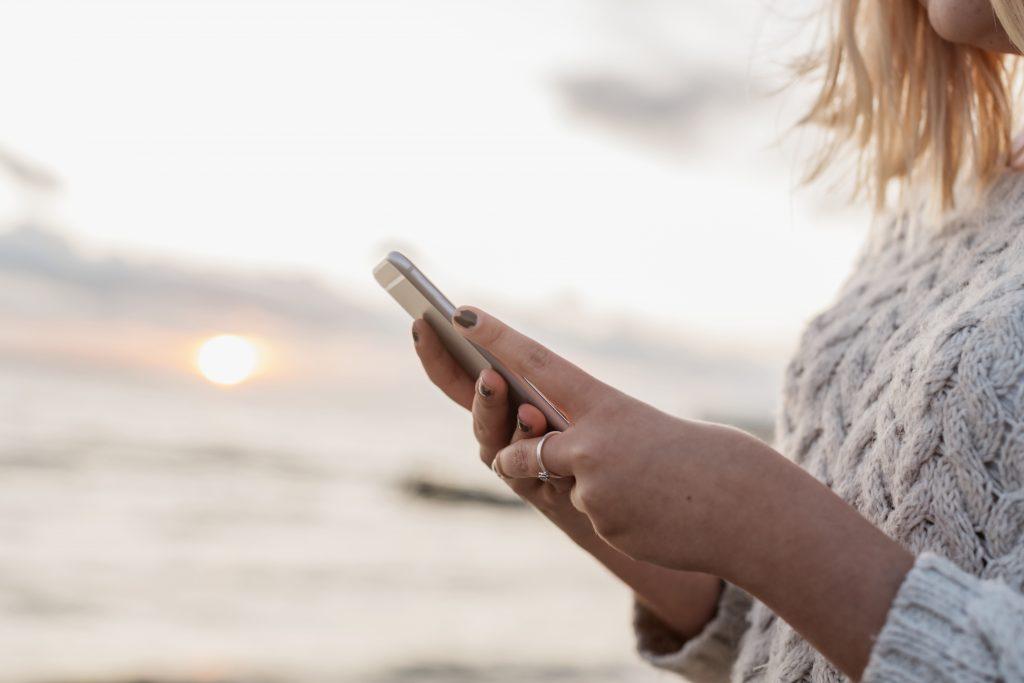 En dame med telefon i hånden og solnedgang