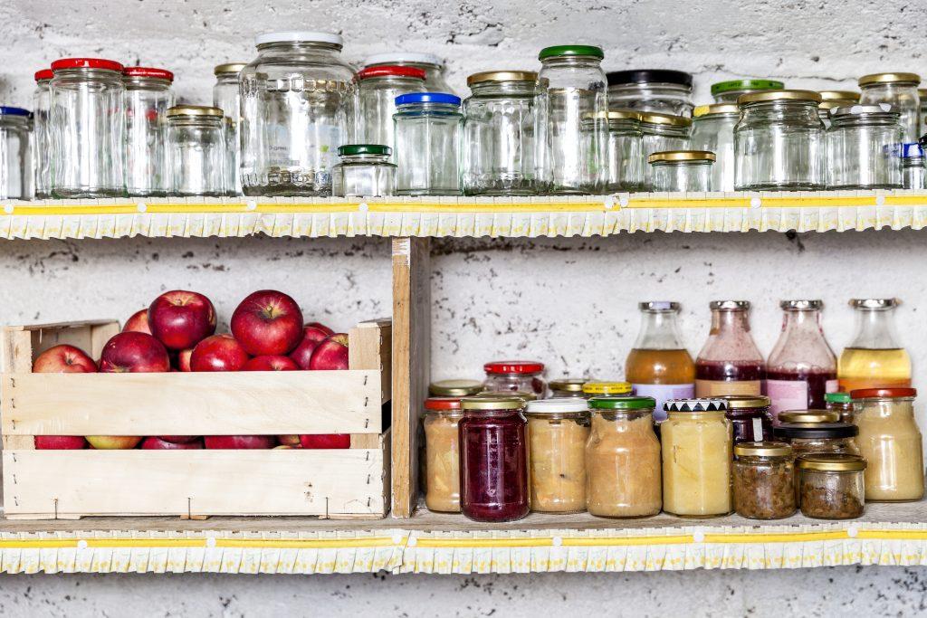 Syltetøyglass i hyller og epler i kasse