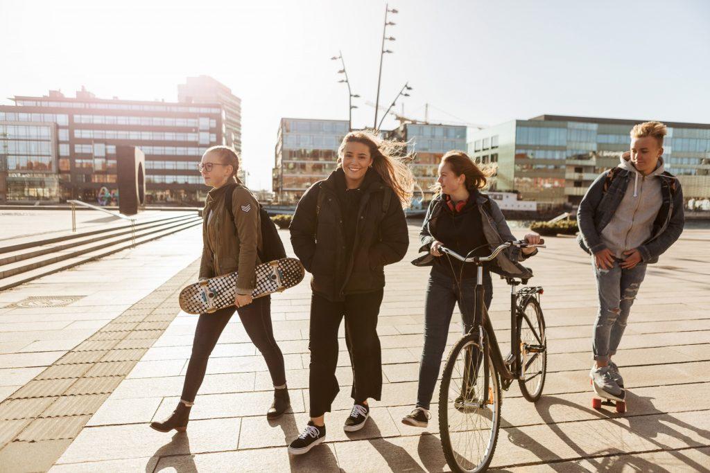 Unge venner går med skateboards og sykkel på torg