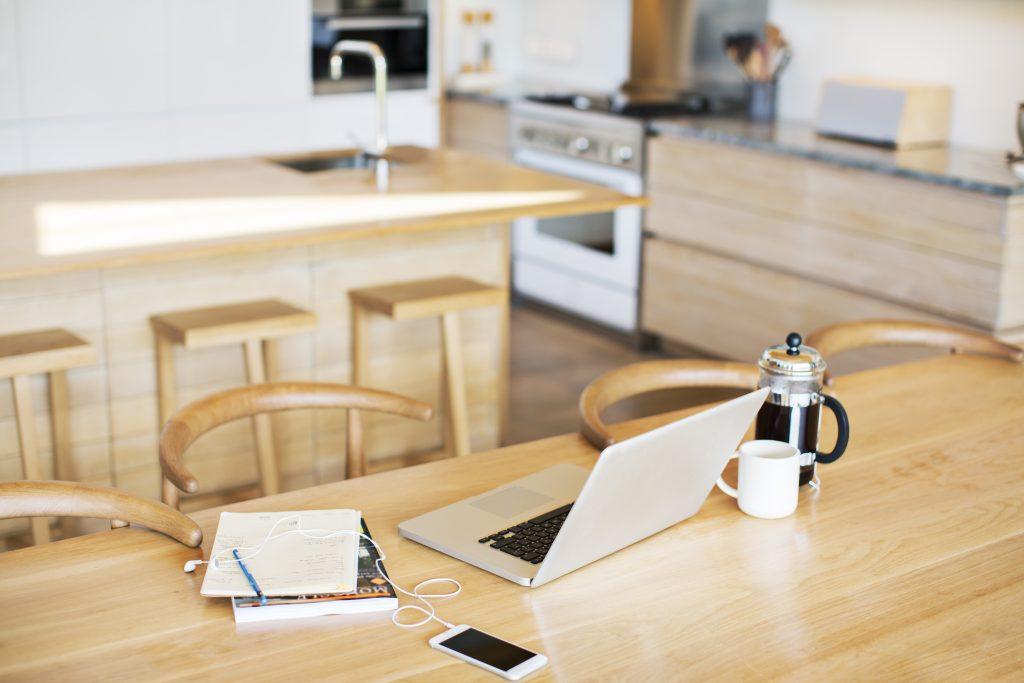 Kaffekopp på kjøkkenet med pc