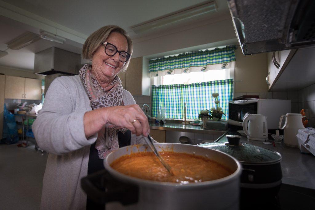 Dame lager suppe i stor kjele