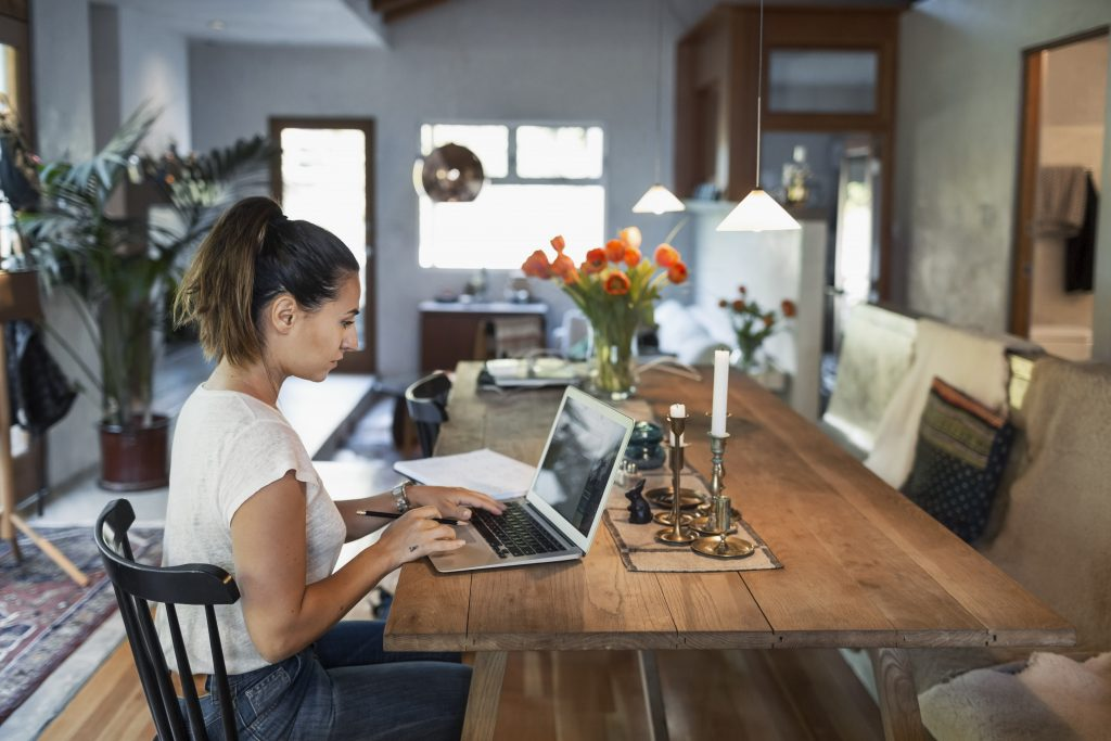 Dame som bruker laptop på kjøkkenet