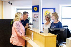 Kunder snakker med to bankmedarbeidere i skranken