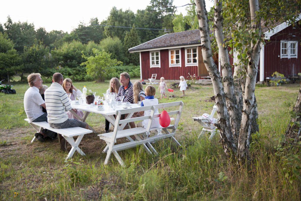 Familie sitter ute forran hytte på vår/sommer