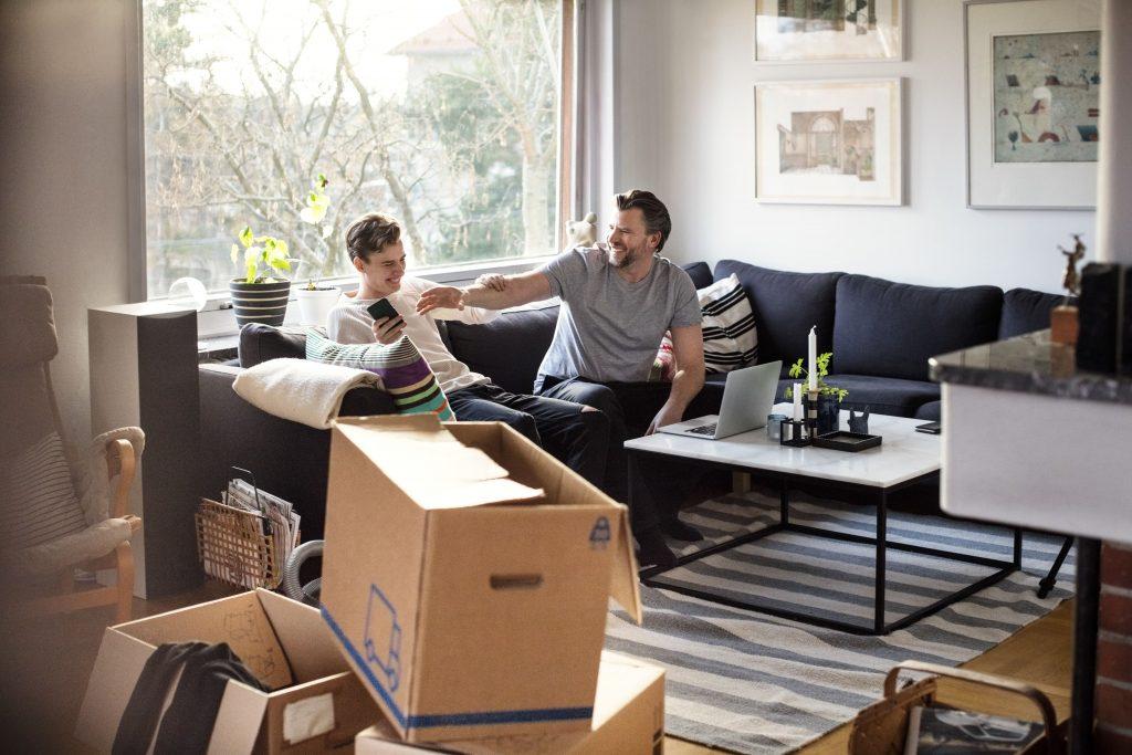 Far og sønn i stue med flytteesker