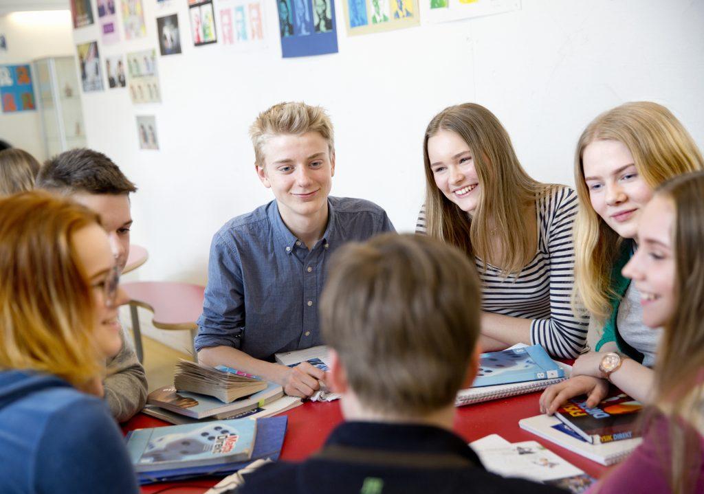 Ungdomskoleelever som sitter rundt et bord