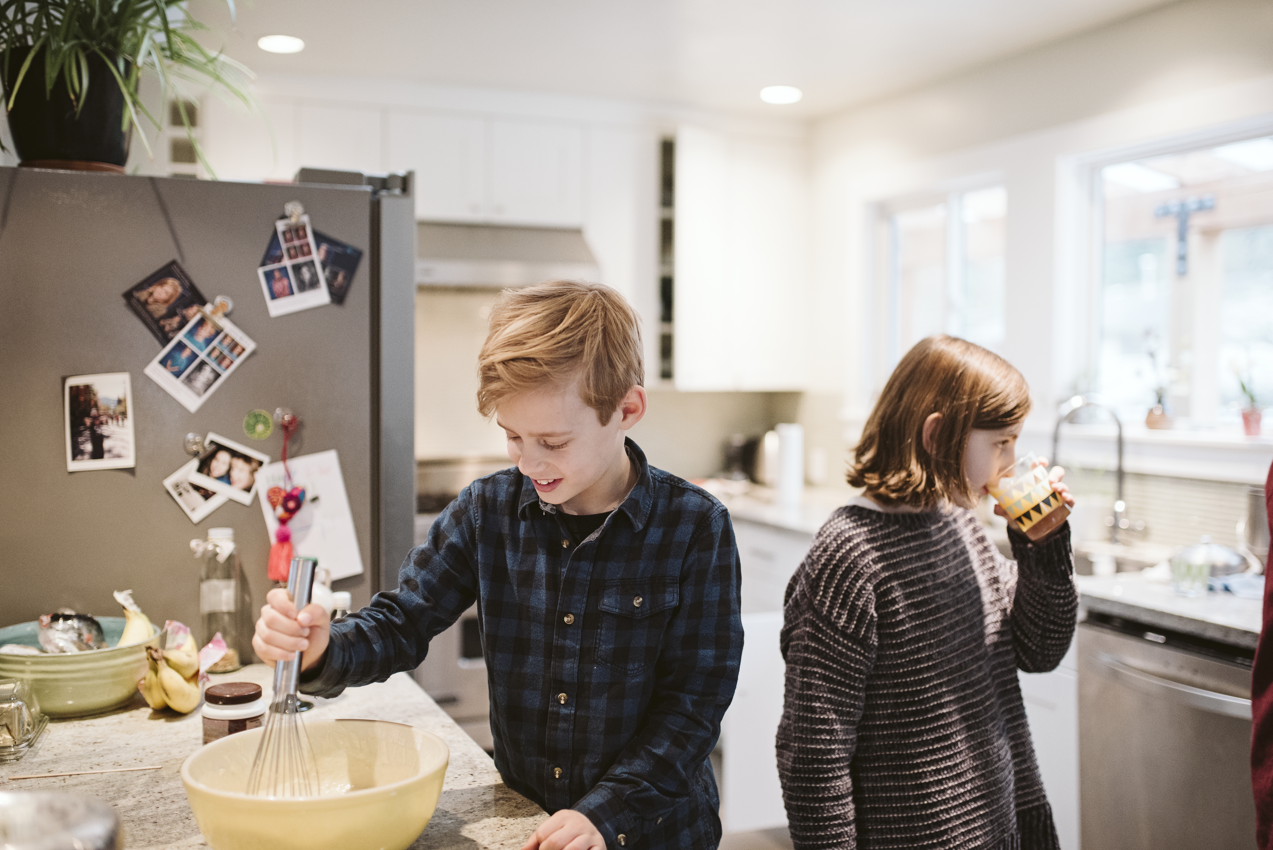 2 barn lager mat og drikker jus på kjøkken