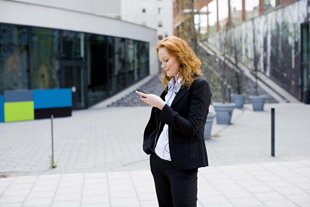Dame med rødt hår iført dress står med mobil i hånden foran forretningsbygg.