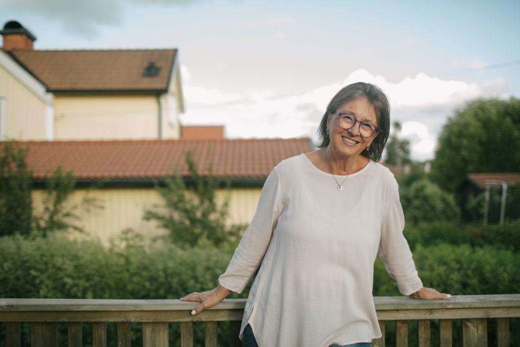 Eldre kvinne på terrassen smiler