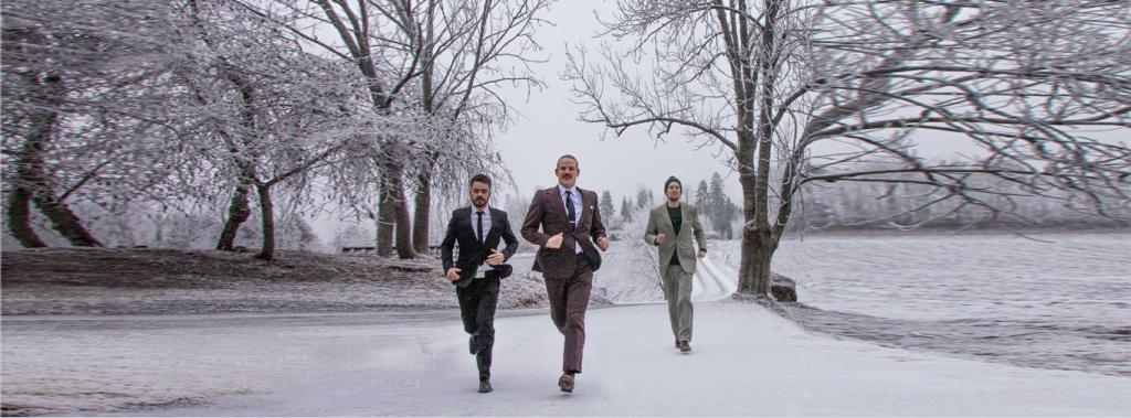 Tre menn i dress løper om vinteren ned en vei.