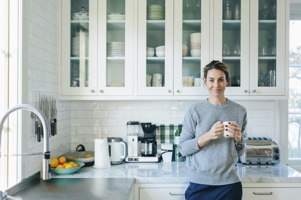 Ung kvinne drikker kaffe hjemme på kjøkken