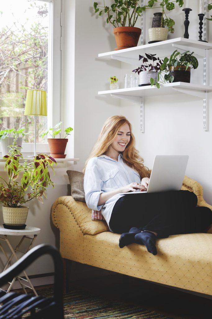 Smilende kvinne bruker bærbar pc i soffa