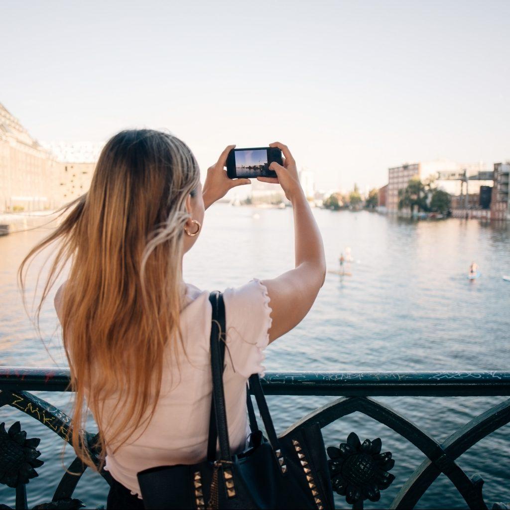 Kvinne tar bilde på elv i by med smartphone