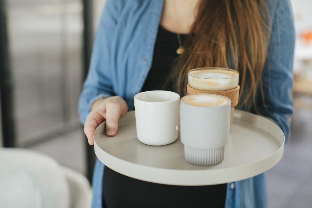 Kvinne med kaffe på brett
