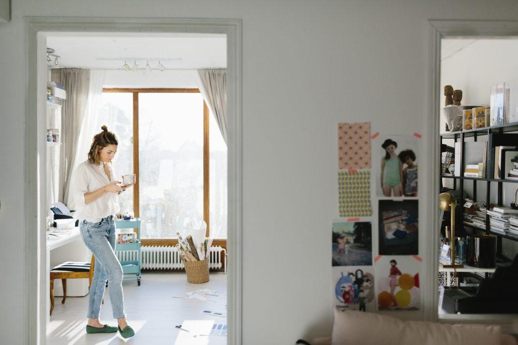 Kvinne står i stuen med mobiltelefon