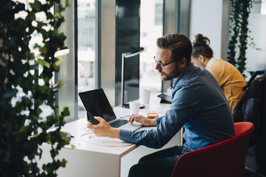 Mann sitter på høy stol med telefon og laptop