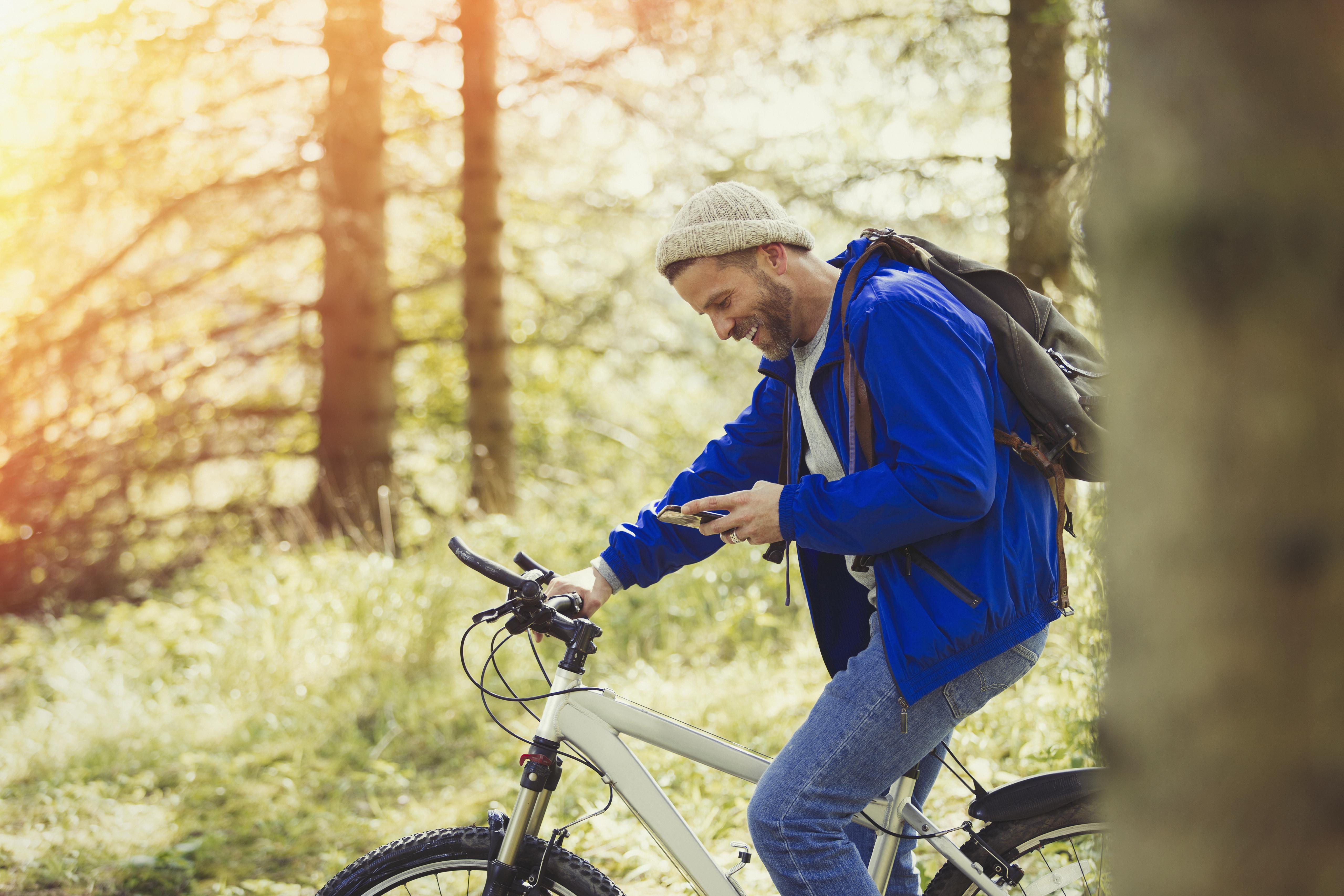Mann sykler i skogen og ser på mobil