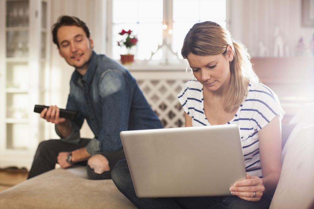 Mann og kvinne sitter med PC i stua