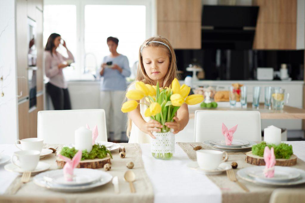 Liten jente dekker bordet til påske med gule liljer