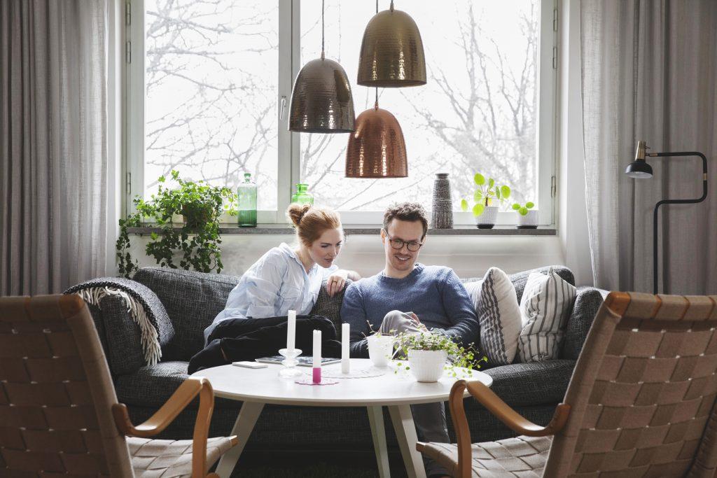 Par som sitter i en sofa i stuen og ser på en telefon