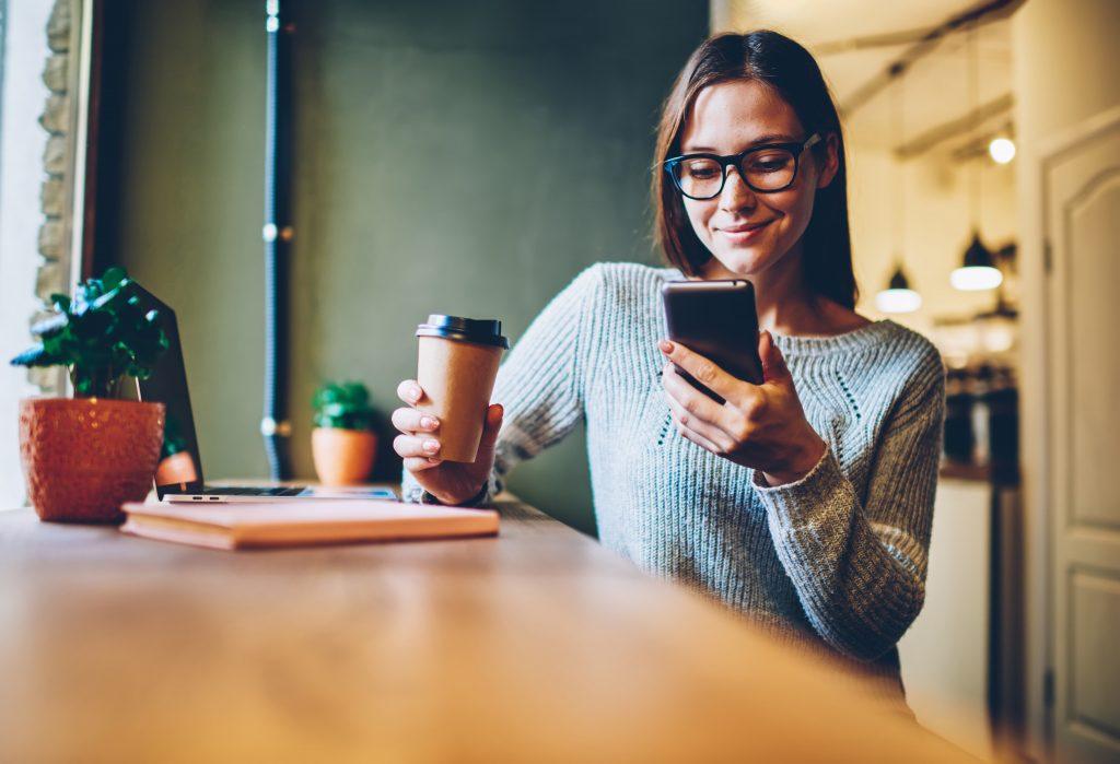 Dame holder mobiltelefon og kaffekopp. Står ved bord eller benk.