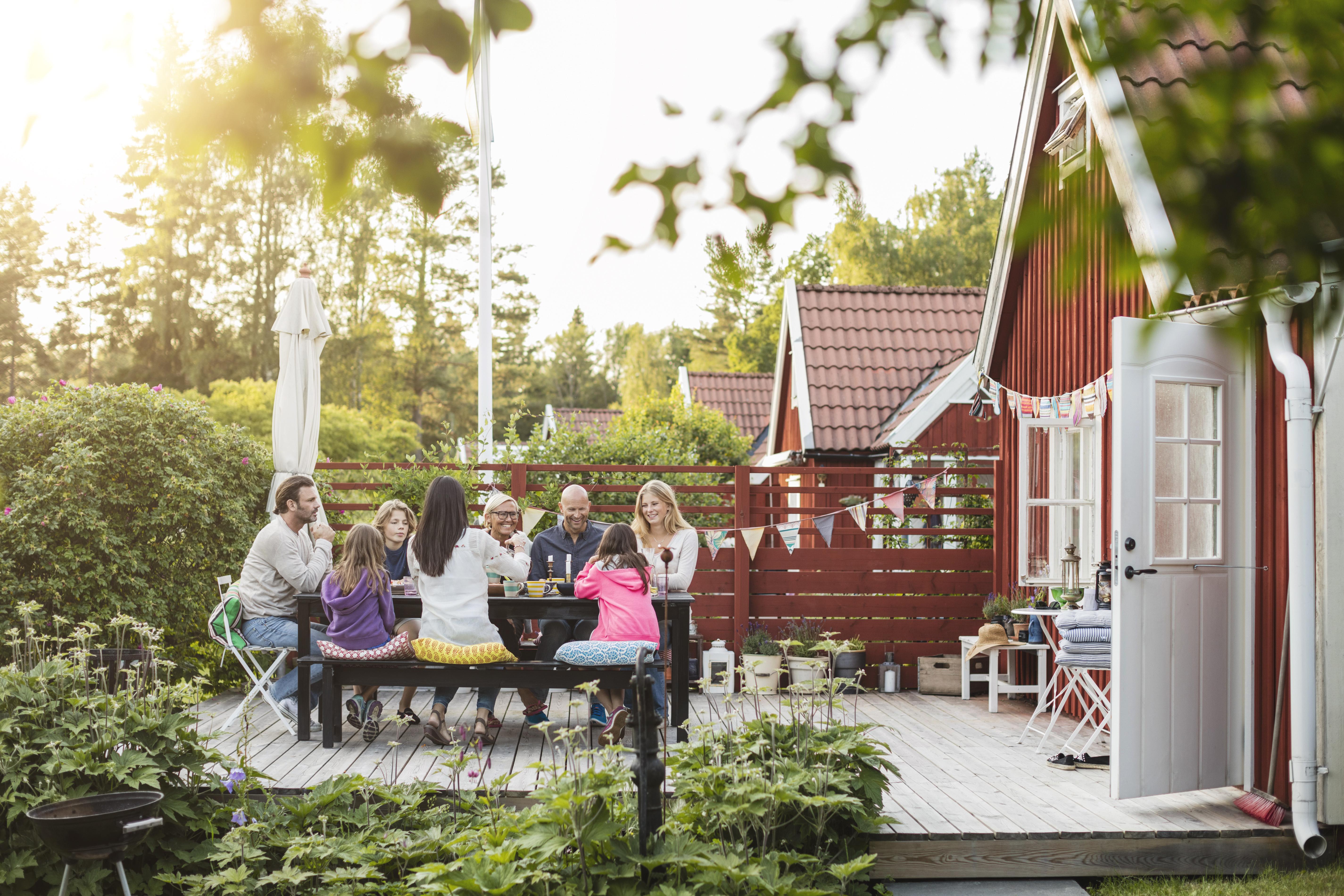 Mennesker sitter ved spisebord ute på veranda på baksiden av huset.