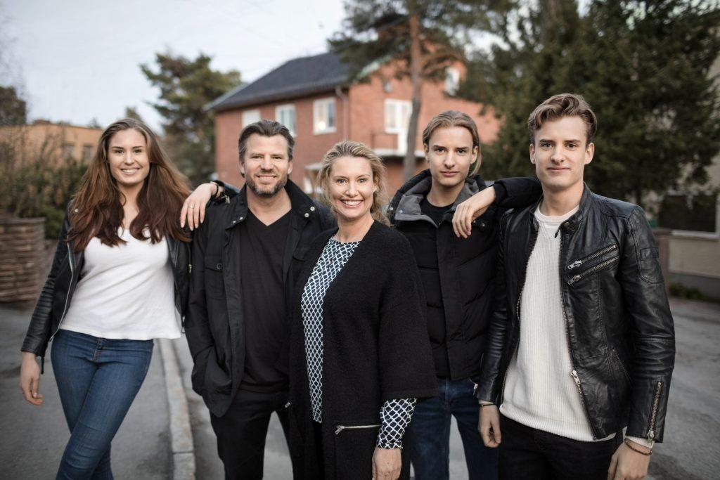 To voksne og tre eldre barn smiler til kamera på gaten